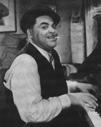 Photograph of Fats Waller playing the piano and wearing his famous bowler hat, inspired by his mentor, Willie the Lion Smith.