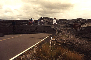 Photo of a lava flow covering a road.