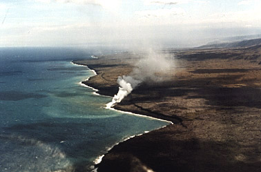 Photo of steam rising from a lava flow entering the ocean.