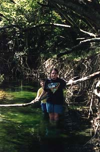 Photograph of Megaera and Malachi in the lush, soupy green water of Madog River.