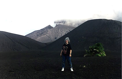 Photograph of Brenna Lorenz in front of a small cinder cone near the vent of Mt. Pagan.